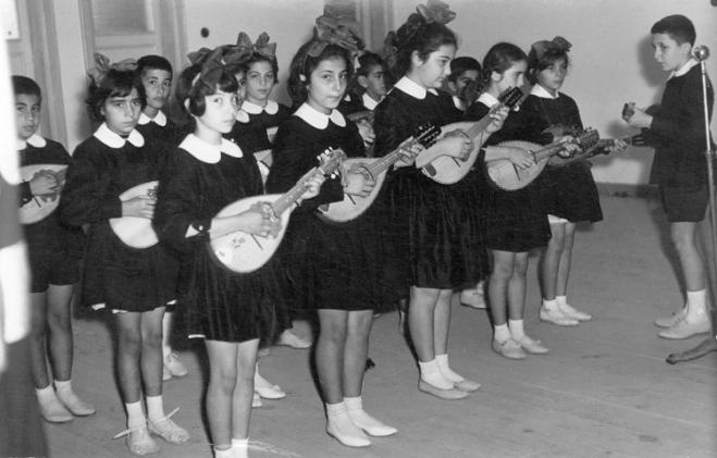 """İlkokulumuzun """"parlak"""" çocuklardan oluşan mandolin grubu (şef konumundaki ben): Erkek saçları alabros, önlükler koyu siyah, yakalar kolalı. Bu fotoğraf çekilmeden önce birkaç öğretmen bizleri, parmakların aynı perdeye basmasından ayaklarımızın aynı pozisyonda durmasına kadar, aynılaştırmak için epeyce uğraşmıştı. Duruş ve bakışlarımızdaki ürkekliğin nedeni odur. Çaldığımız parçalardan biri de """"Neşeli ol ki genç kalasın"""" idi."""